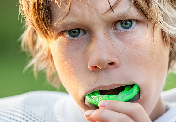 Teen boy placing green mouthguard