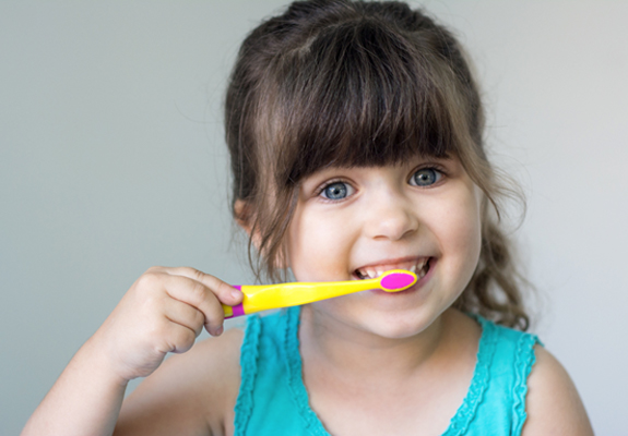 A little girl brushing her teeth after seeing a children's dentist in Fanwood
