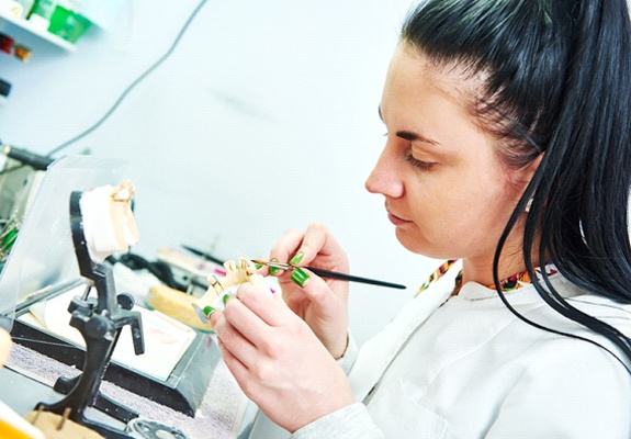 A lab technician making a custom restoration