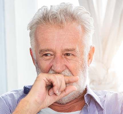 Older man covering his mouth