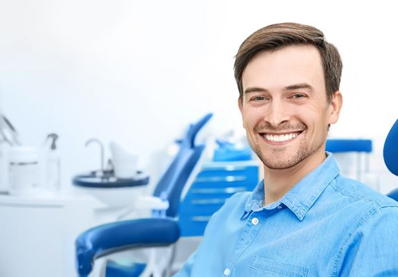 Man with blue shirt smiling in dental chair