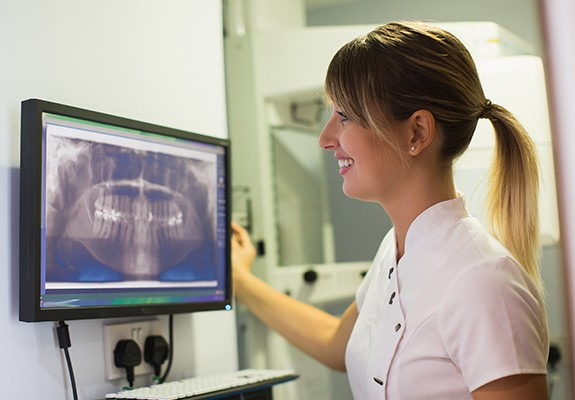 Team member looking at digital dental x-rays