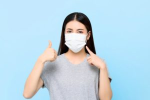 young woman wearing face mask and giving thumbs up against light blue background