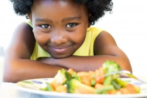 little girl smiling with a plate of vegetables